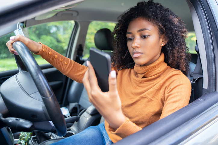 A young woman drives a car and texts on her phone