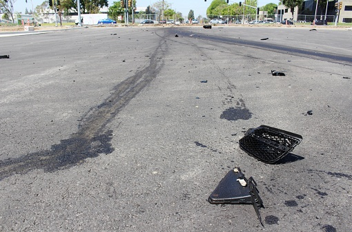 Broken pieces from a crashed car and tire marks indicate a hit-and-run crash.